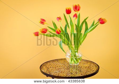 Red Tulips In A Vase On Mosaic Table.