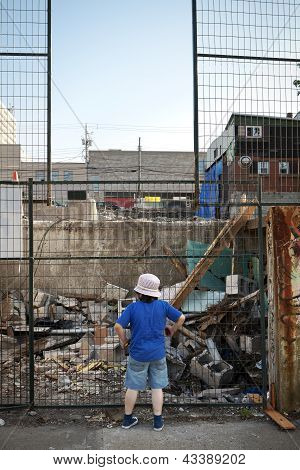 Boy Looking at Demolition Site Through Fence
