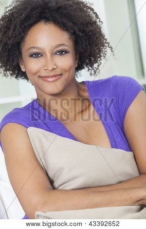 A beautiful mixed race African American girl or young woman looking happy and thoughtful holding a cushion