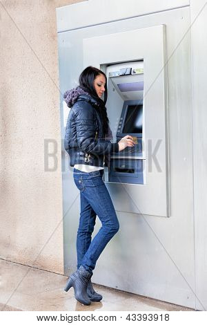 Girl get cash from an ATM on a city street