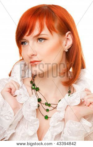 Close-up of beautiful woman face with red hair and green beads