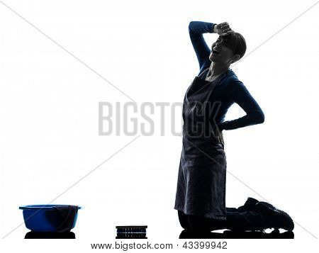one caucasian woman maid cleaning backache washing floor   in silhouette studio isolated on white background
