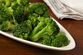 Freshly steamed broccoli on plate with fork and napkin in background. Macro with shallow dof.