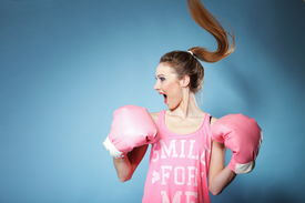 pic of hair motion  - Female boxer model wearing big fun pink gloves playing sports boxing hair motion blue background - JPG