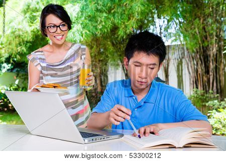 Chinese thoughtful mother brings her son some food, he makes homework for the next day at school and is concentrated