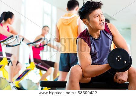 Chinese Asian group of men and woman doing sport exercise or training in fitness gym with barbell and weights for more power