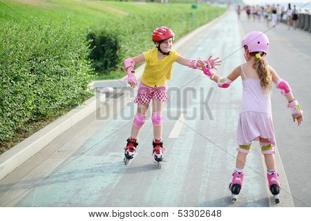 Two girls in roller skates, knee and elbow pads ride on rollers and give each other a high five