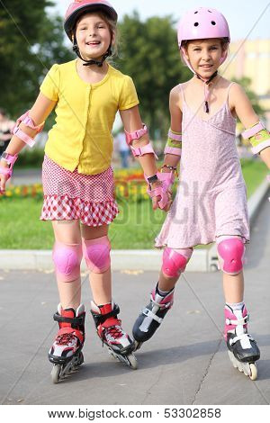 Two girls wearing helmets, elbow pads and knee pads ride on roller skates in the park