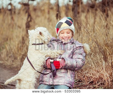 little cute girl with her dog breed White Terrier  in a field in autumn