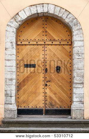 Old Uncolored Wooden Door In Old Building Facade With Arch. Tallinn, Estonia