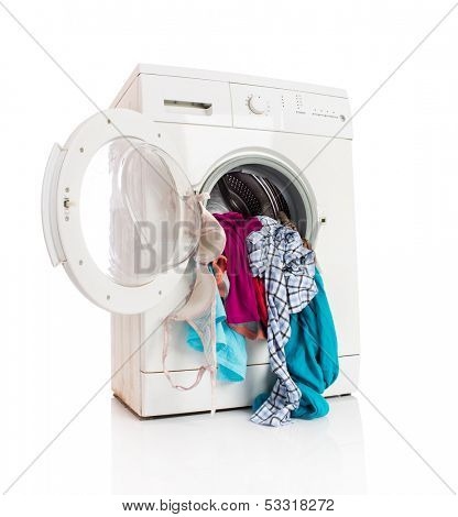 Washing machine with clean linen on a white background
