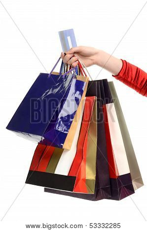 Female hand holding many shopping bags and a credit card.