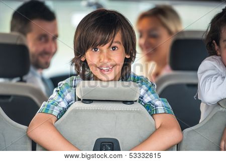 Cute smiling boy in the car backseat with his parents in background