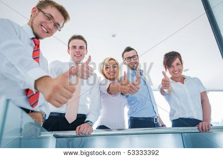 A team of smiling business people showing thumbs up