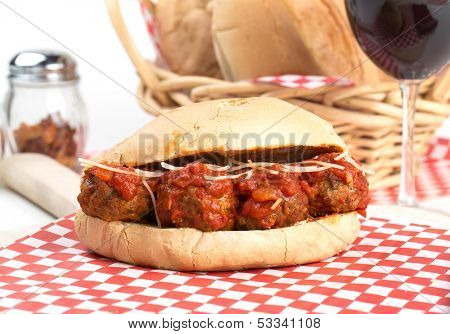 Delicious Italian meatball with marinara sauce sub sandwich, with a basket of crusty rolls and a glass of red wine in the background