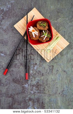 Asian meatballs, garnished with pea shoots and radish julienne, in a red bowl on bamboo tray with chopsticks, against natural slate background. Space for your text