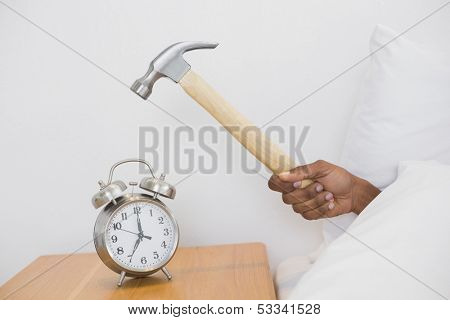 Close up of an Afro man's hand smashing alarm clock with hammer in bed at home