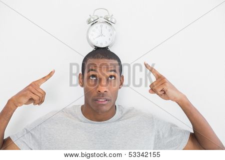 Close up of a man pointing at alarm clock over his head against white background