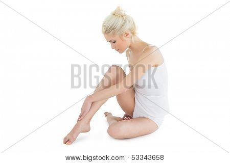Full length side view of a toned blond sitting over white background