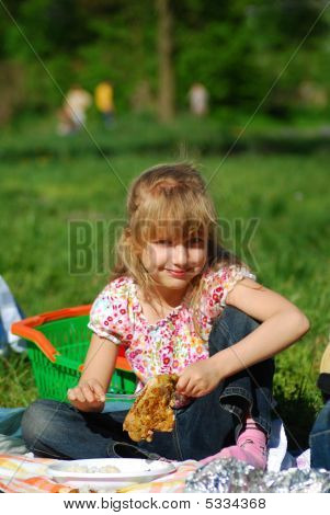 Young Girl Eating On Picnic