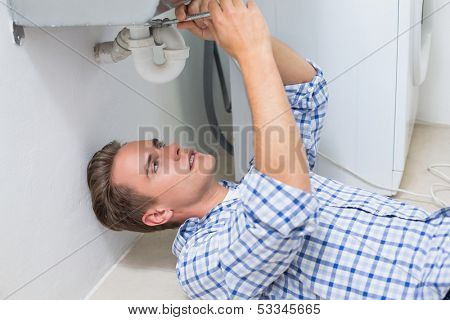 Side view of a young plumber repairing washbasin drain in bathroom
