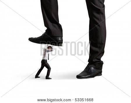small businessman under big leg his boss. isolated on white background