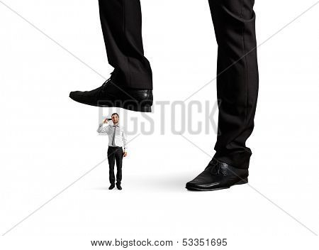 small desperate businessman with gun under big leg his boss. isolated on white background
