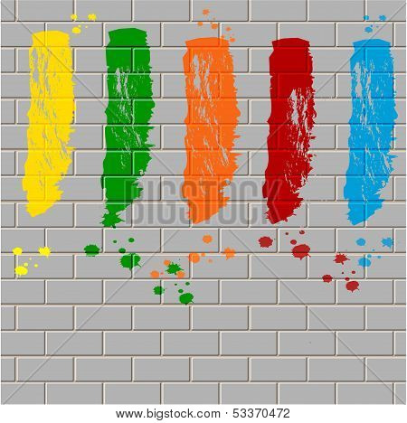 spots of varicoloured paint on a gray brick wall