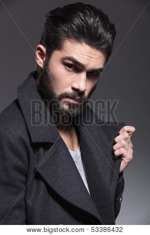 closeup picture of a fashion man with long beard holding his collar and looks at the camera