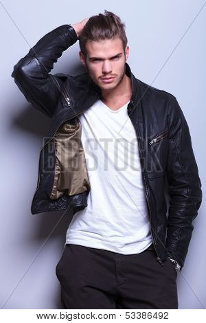 fashion man in leather jacket passing his hand thorugh his hair, on gray background