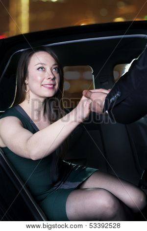 Young, glamorous woman being helped out of her car
