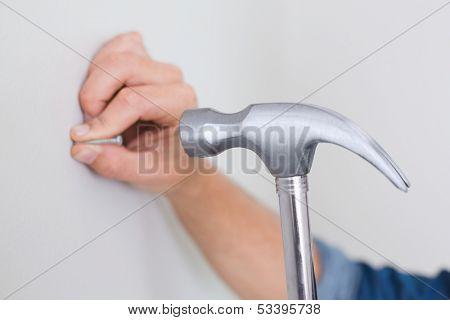 Extreme Close up of a handyman hammering nail in wall