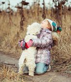 picture of westie  - little cute girl with her dog breed White Terrier walking in a field - JPG