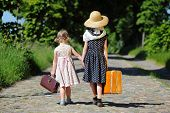 stock photo of tree lined street  - Two little girls walking with her luggage at a tree - JPG