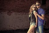 pic of denim jeans  - Couple of young people in jeans clothes posing outdoors over brick wall - JPG