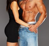 stock photo of hunk  - Young woman embracing man with naked muscular torso - JPG