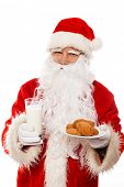 Santa Claus with oatmeal cookies and glass of milk isolated on white background