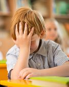 stock photo of redhead  - Little redhead schoolboy behind school desk during lesson - JPG