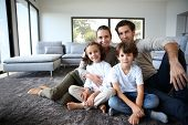 stock photo of cheer  - Happy family portrait at home sitting on carpet - JPG