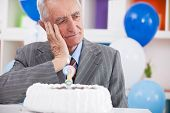 Sad senior man forgot how old is looking at birthday cake with a question mark