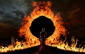 stock photo of satan  - Woman in red dress at the gate of hell - JPG
