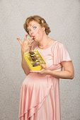 image of finger-licking  - Single pregnant woman with candy licking her fingers - JPG