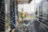 image of refraction  - Glass broken cracks splinters in front of the bus station - JPG