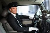 stock photo of adults only  - Handsome smiling chauffeur driving limousine - JPG