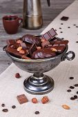 picture of melchior  - Chocolate in a metal vase on a background of gray canvas and wood - JPG