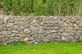 stock photo of old stone fence  - background pattern gray color of modern style design decorative fence real stone wall surface with cement on green grass field - JPG