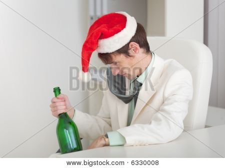 Drunken Man In Christmas Cap With Bottle In A Hand