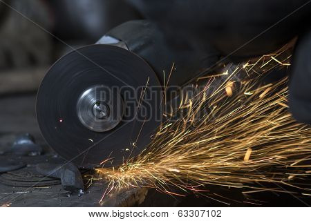 Electric wheel grinding on steel structure by worker in factory