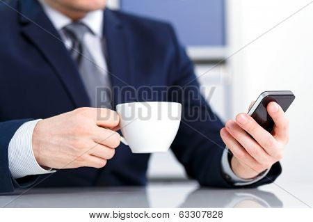 Businessman Holding A Mobile Phone And Coffee