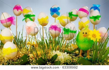 Easter eggs with multicolored ribbons on wooden sticks and green grass with poults decorations